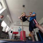 Dziecko na zajęciach ju-jitsu wspina się po linie